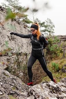 Jogger sportif féminin marchant sur des pierres