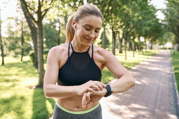 Jogging du matin belle femme sportive en vêtements de sport et écouteurs en regardant sa montre vérifiant le