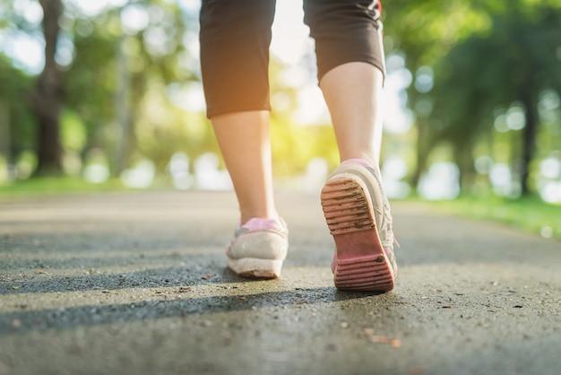 Jogging des femmes avec des chaussures sales dans un parc