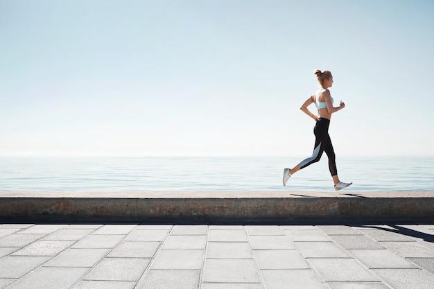 Jogging jeune femme qui court sur le rivage