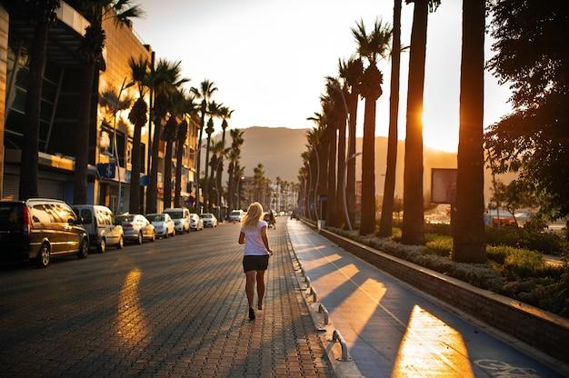 Jogging matinal d'une jeune femme sur la route dans la ville de marmaris.turquie