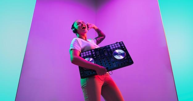 Joie. jeune musicienne au casque sur fond violet à la lumière du néon. concept de musique, passe-temps, festival, divertissement, émotions. hôte joyeux, dj, portrait d'artiste.