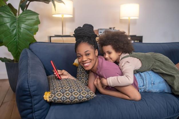 Joie. petite fille afro-américaine étreignant une jeune mère heureuse avec un smartphone à la main allongé sur un canapé à la maison