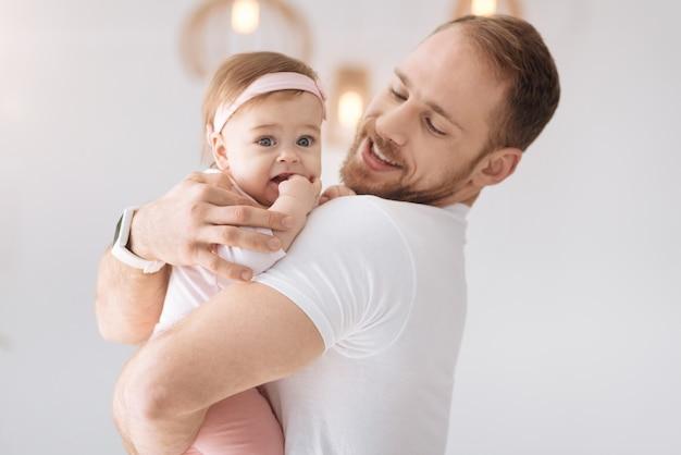Joie pure. mignonne petite fille aimable couchée dans les mains du jeune père et regardant ailleurs tout en exprimant la positivité