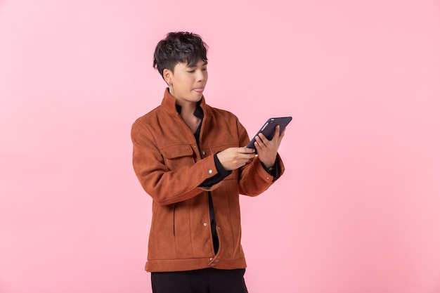 Une joie réussie et expresse asiatique un homme beau jeune utilisant une tablette sur les yeux de côté regardant la caméra amoureuse isolée sur fond de studio espace copie vierge rose.