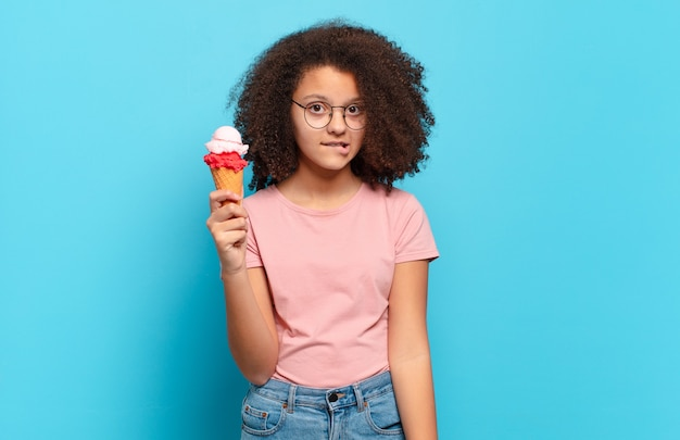 Joli adolescent afro à l'air perplexe et confus, mordant la lèvre avec un geste nerveux, ne connaissant pas la réponse au problème. concept de crème glacée d'été