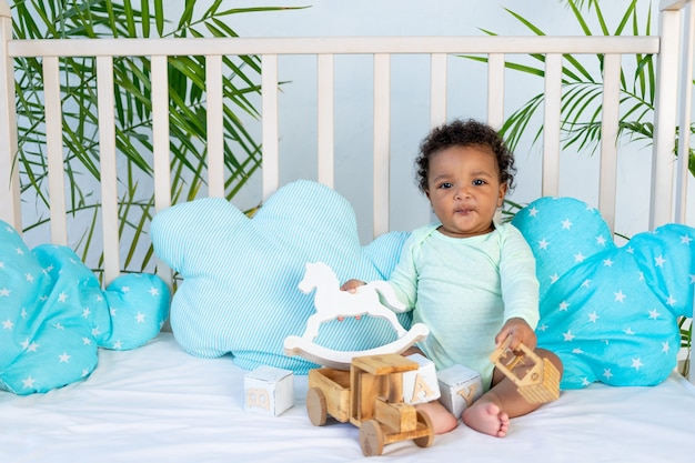 Un joli bébé africain est assis dans son lit à la maison sur un lit en coton bleu et joue avec des jouets en bois, un cheval et une machine à écrire.