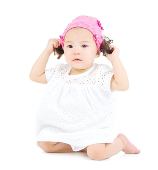 Joli bébé asiatique assis sur le sol.