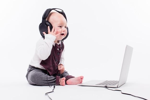Joli bébé assis devant un ordinateur portable portant des écouteurs sur w