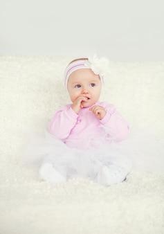 Joli bébé assis en robe dans la chambre