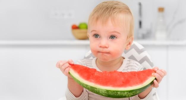 Joli bébé blond caucasien d'un an déjeuner dans la cuisine en mangeant des aliments sains melon d'eau manger soi-même