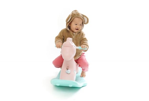 Joli bébé chevauchant un cheval de bois blanc