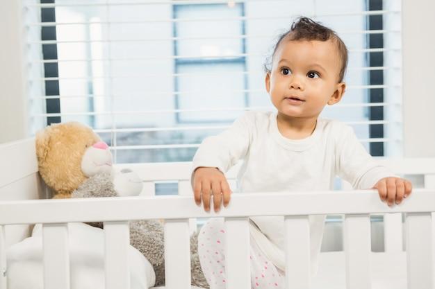 Joli bébé dans la crèche regardant autour