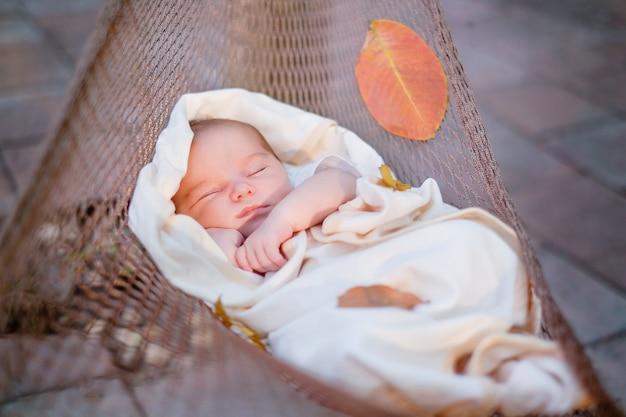 Joli bébé dormant dans un hamac marron à l'extérieur