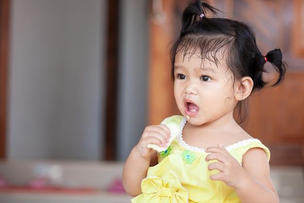 Joli bébé enfant asiatique fille mangeant de la mangue