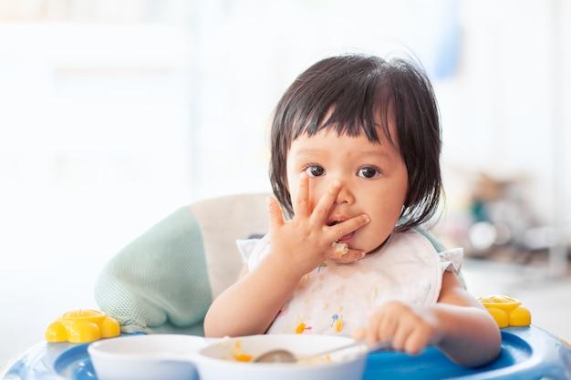 Joli bébé enfant asiatique fille manger des aliments sains par elle-même