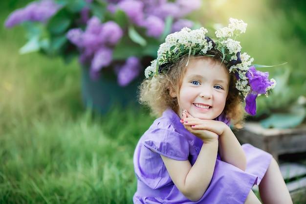 Joli bébé est assis sur une pelouse aux cheveux bouclés à l'âge de 4 ans