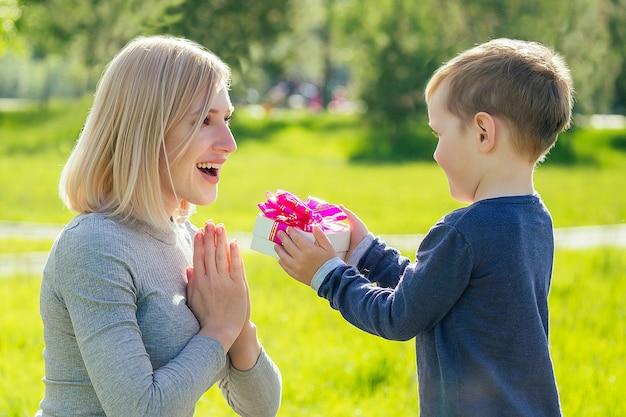 Joli bébé (fils) offre un coffret cadeau à sa belle mère blonde dans le parc sur fond d'herbe verte. concept de fête des mères