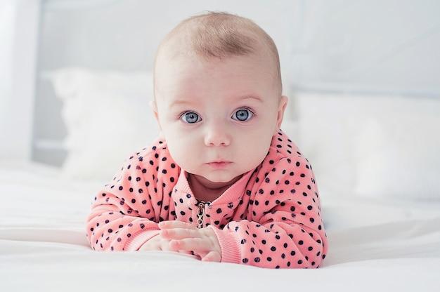 Joli bébé sur le lit blanc