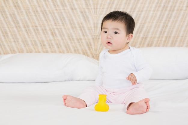 Joli bébé sur le lit en regardant autour