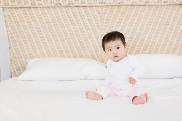 Joli bébé sur le lit en regardant la caméra