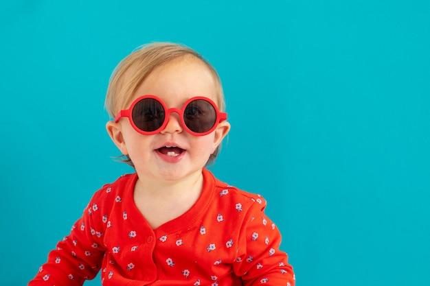Joli bébé à lunettes de soleil rouges sourire