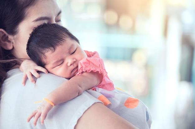 Joli bébé nouveau-né asiatique dormant sur l'épaule de la mère.