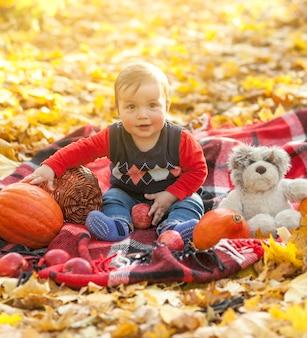 Joli bébé avec ours en peluche sur une couverture
