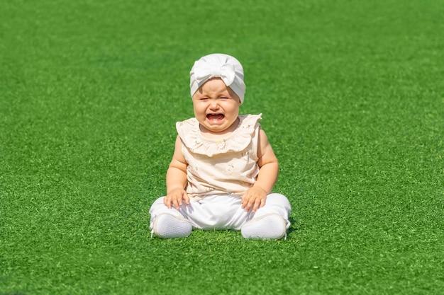 Joli bébé pleurant assis au milieu d'une pelouse verte