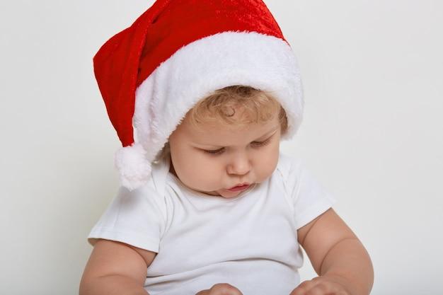Joli bébé portant des vêtements de noël jouant à l'intérieur, regardant attentivement quelque chose dans ses mains, a les cheveux blonds ondulés
