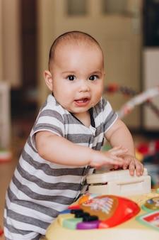 Un joli bébé potelé se tient debout et joue avec une table de musique pour enfants. beaucoup de jouets colorés partout.