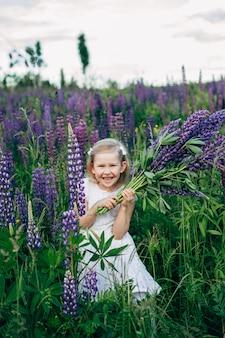 Joli bébé en robe blanche dans un champ de lupins