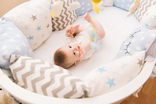 Joli bébé se trouve dans un lit rond blanc. garderie légère pour les jeunes enfants.