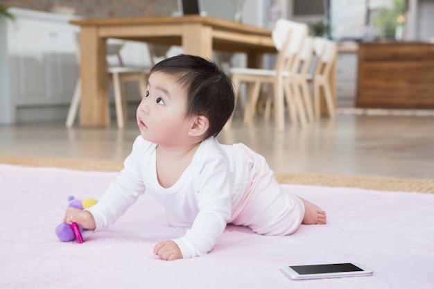 Joli bébé sur le tapis en levant