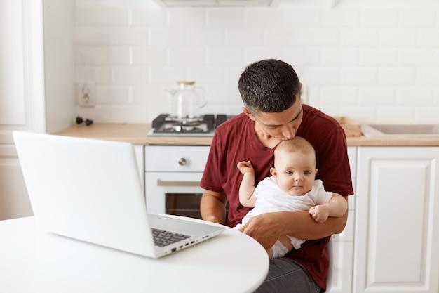 Joli bel homme aux cheveux noirs portant un t-shirt décontracté bordeaux, embrassant sa charmante fille, travaillant sur un ordinateur portable tout en faisant du babysitting, posant dans une cuisine blanche.
