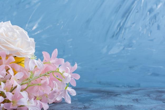 Joli bouquet de fleurs blanches et roses sur fond bleu.
