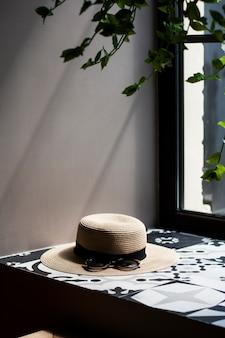 Joli chapeau de chaume pour femmes avec bande noire et lunettes de soleil allongé sur le rebord de la fenêtre, une plante verte et une fenêtre