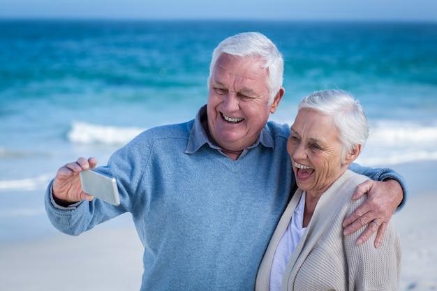 Joli couple d'âge mûr prenant selfie sur la plage