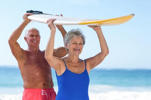 Joli couple d'âge mûr tenant une planche de surf au-dessus de leurs têtes