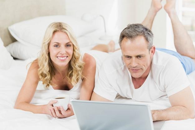 Joli couple à l'aide d'un ordinateur portable au lit dans leur chambre