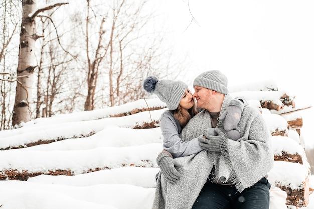 Joli couple amoureux assis sur le journal, forêt d'hiver. ouvrages d'art.