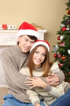Joli couple amoureux près de l'arbre de noël. femme et homme célébrant noël