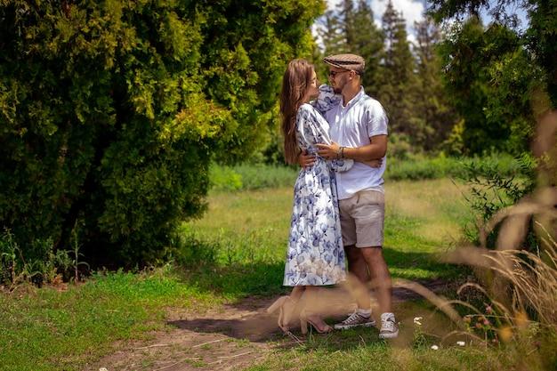 Joli couple amoureux se tient la main et se regarde dans le jardin verdoyant