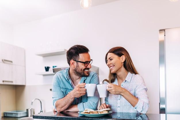 Joli couple applaudir avec une tasse de café ou de thé.