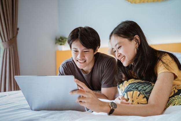 Joli couple asiatique se détendre sur le lit à l'aide de l'ordinateur portable à la maison dans la chambre ensemble