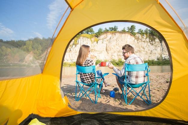 Joli couple assis près de la tente jaune