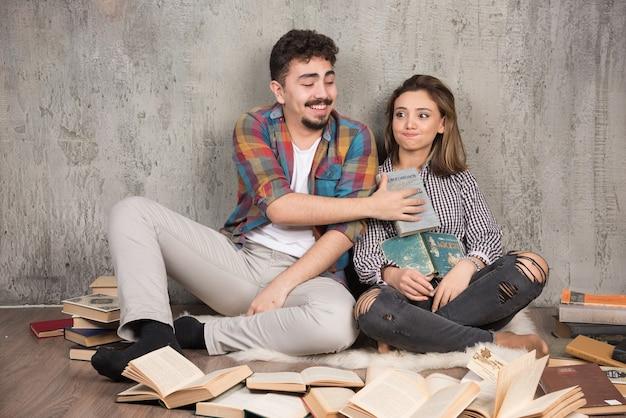 Joli couple assis sur le sol avec beaucoup de livres