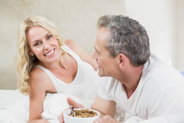 Joli couple ayant un bol de céréales dans leur lit