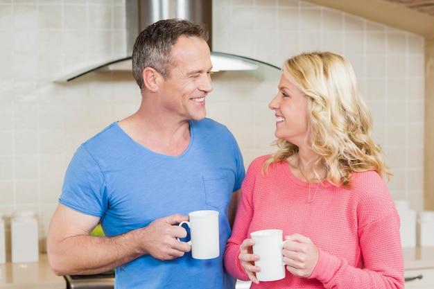 Joli couple ayant une tasse de thé dans la cuisine