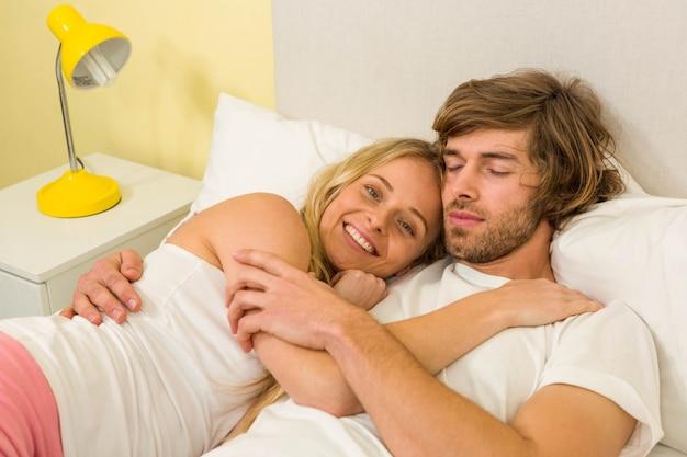 Joli couple câlin sur leur lit dans la chambre